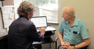 Dr. Kirk Hollohan with his patient viewing patient data on his computer